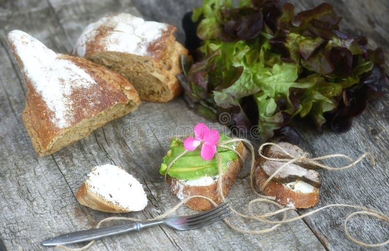 Panini puri con carne al forno e gli avocado su un fondo di legno approssimativo Alimento semplice dell'azienda agricola fotografia stock libera da diritti