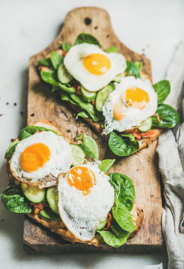 Panini sani della prima colazione sul bordo di legno rustico sopra fondo grigio fotografie stock