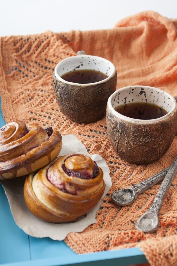 Panini saporiti con inceppamento e due tazze di tè su un backgro di legno blu immagine stock libera da diritti