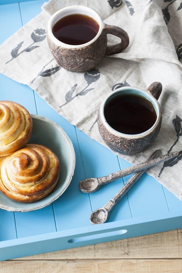 Panini saporiti con inceppamento e due tazze di tè su un backgro di legno blu immagini stock