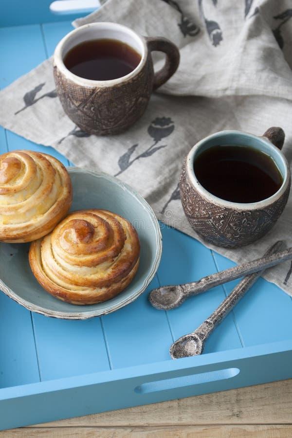 Panini saporiti con inceppamento e due tazze di tè su un backgro di legno blu fotografia stock