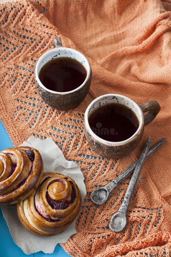 Panini saporiti con inceppamento e due tazze di tè su un backgro di legno blu immagine stock