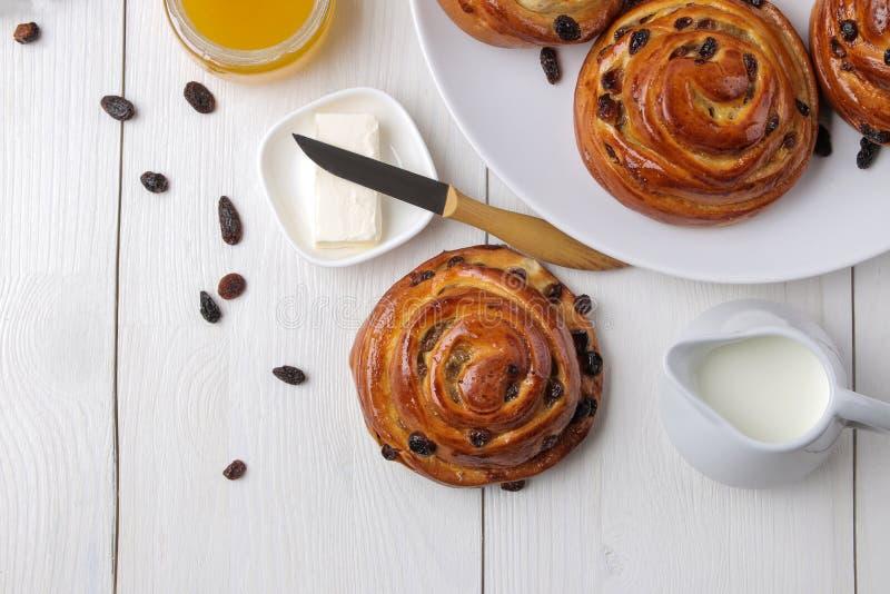 Panini saporiti con l'uva passa ed il burro, latte, miele su una tavola di legno bianca Forno fresco Pane della prima colazione V immagini stock libere da diritti