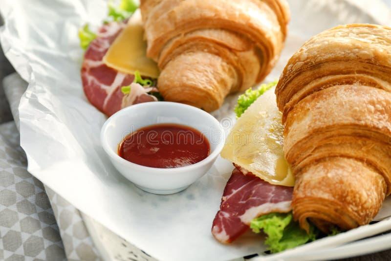 Panini saporiti del croissant con salsa sul vassoio, primo piano immagine stock