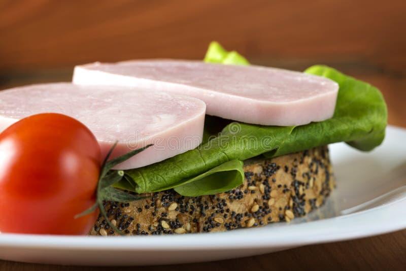 Panino aperto con il prosciutto, l'insalata verde ed un pomodoro sul piatto fotografia stock