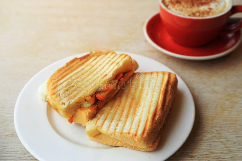 Panino arrostito del formaggio per la prima colazione con la tazza di caffè sulla tavola di legno rustica Fuoco selettivo immagini stock libere da diritti