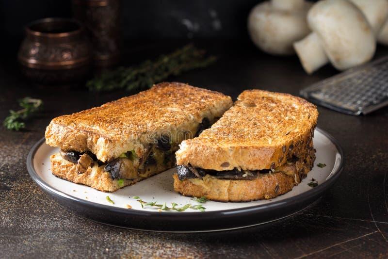 Panino caldo con i funghi, il formaggio e le cipolle verdi, pranzo delizioso, alimento di autunno Fondo scuro immagini stock libere da diritti