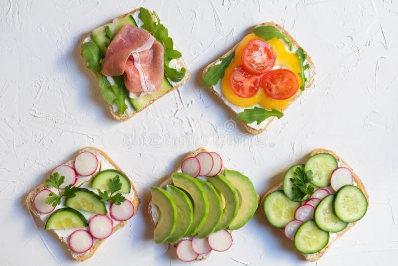 Panino cinque con l'avocado, il ravanello, il cetriolo, il prosciutto crudo, il pepe ed il formaggio fresco, vista superiore dell fotografia stock