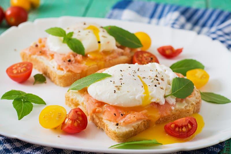 Panino con gli uova affogate con il salmone fotografia stock