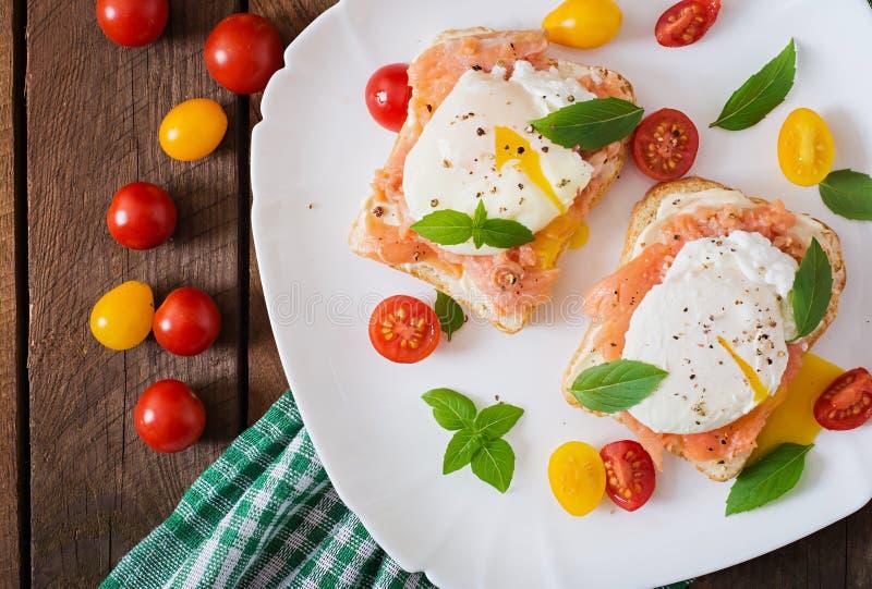 Panino con gli uova affogate con il salmone fotografie stock