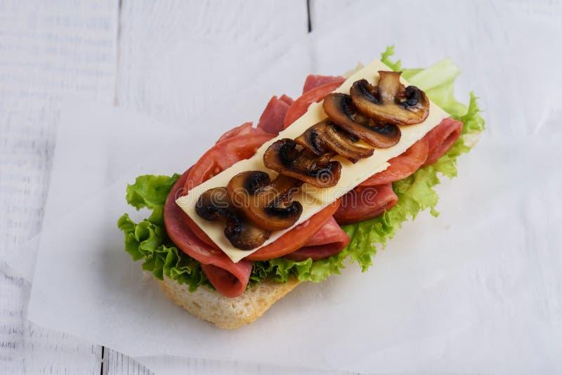Panino con i funghi del formaggio e del fungo prataiolo del pomodoro fotografie stock