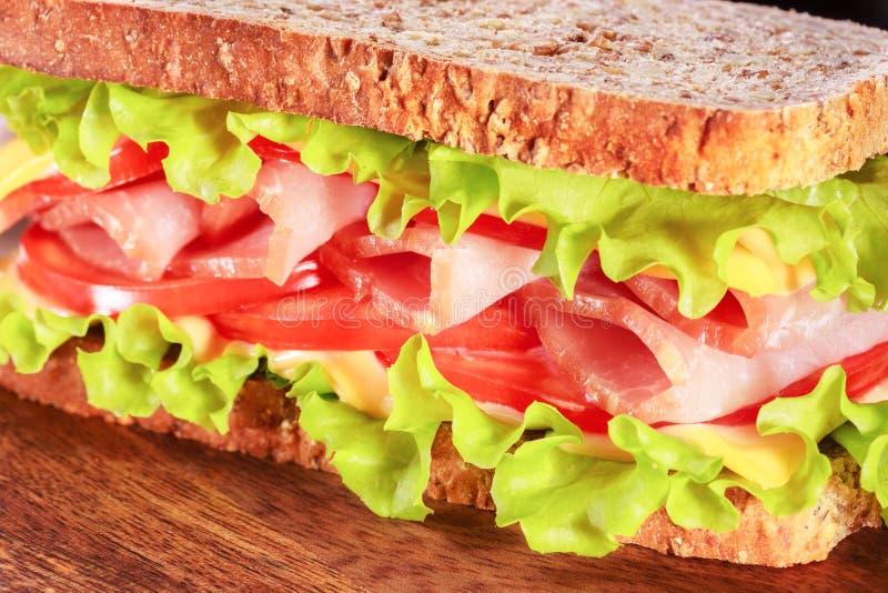 Panino con i pomodori, il formaggio, il prosciutto e l'insalata verde fotografia stock