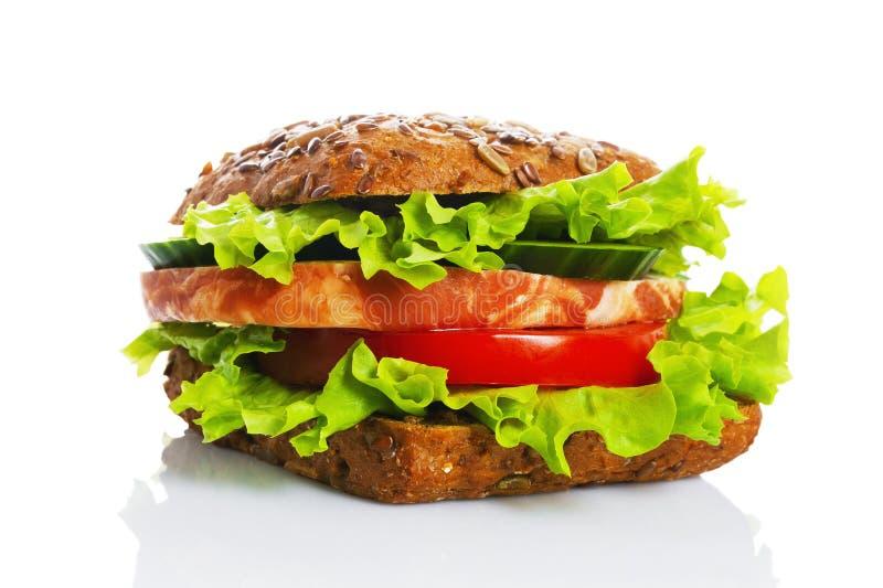 Panino con il pane dei cereali, con il prosciutto e le verdure, insalata verde su un fondo bianco fotografia stock