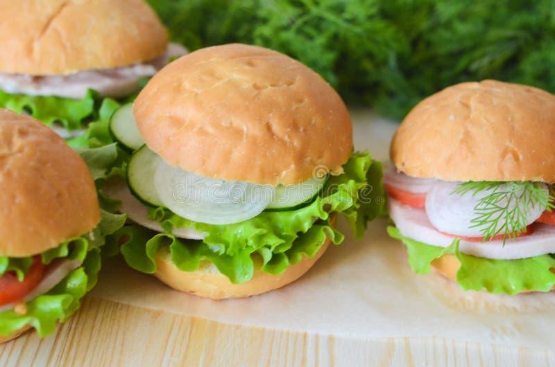 Panino con il pomodoro, insalata del cetriolo e prosciutto e cipolla su un primo piano di legno della tavola nei precedenti fotografia stock libera da diritti