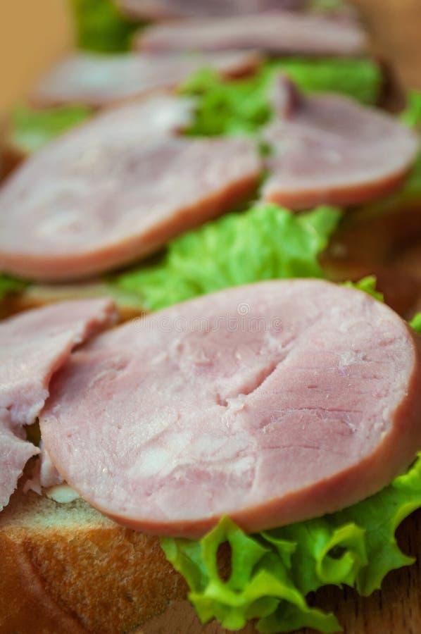Panino con il prosciutto e l'insalata verde fotografia stock