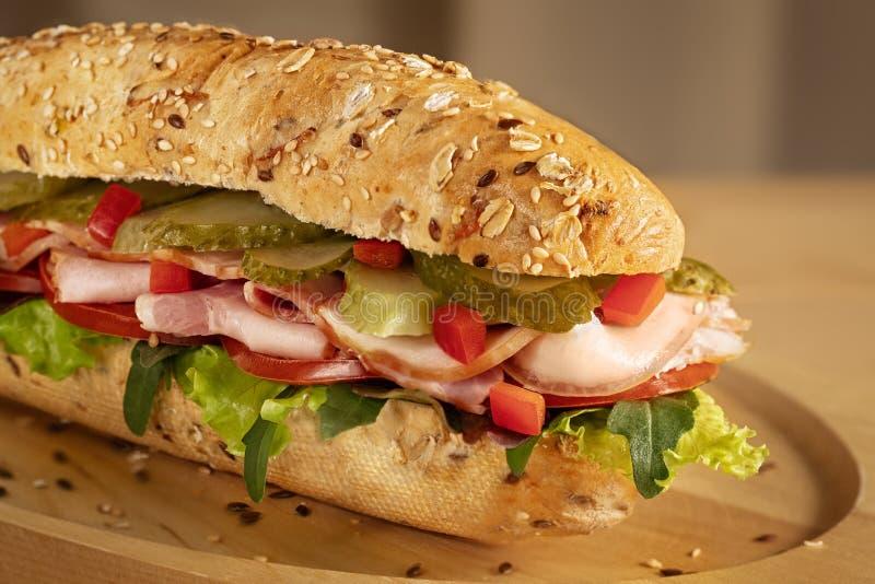 Panino con il prosciutto, i sottaceti, il pomodoro fresco e l'insalata verde fotografie stock