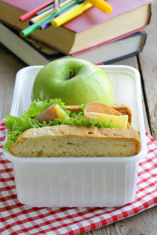Panino con il prosciutto, l'insalata verde e la mela in una scatola fotografia stock libera da diritti