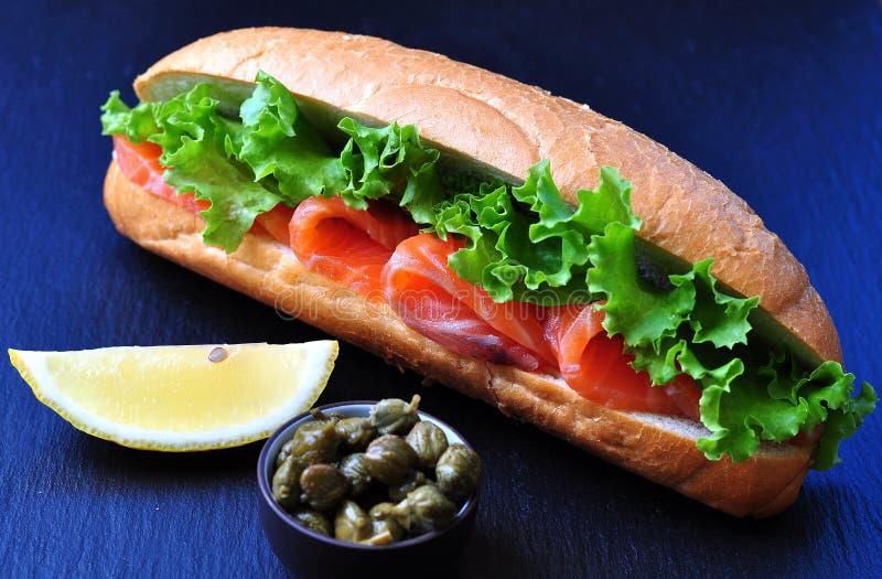 Panino con il salmone marinato, la lattuga, la cipolla bianca ed i capperi fotografia stock libera da diritti