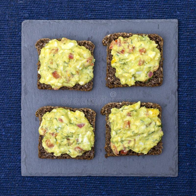 Panino con l'avocado, il pomodoro, l'aneto e l'uovo affogato - concetto sano della prima colazione fotografia stock