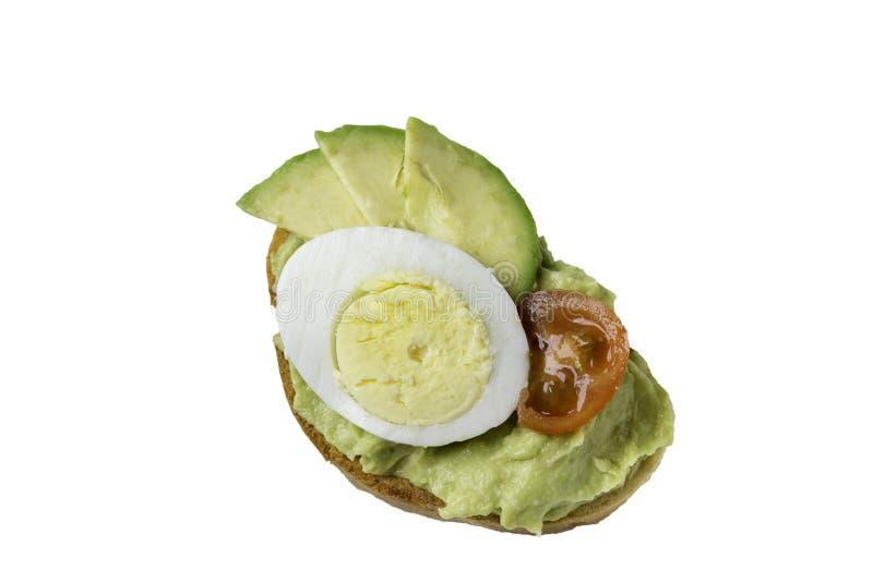 Panino con l'uovo, il pomodoro e l'avocado, isolati su un fondo bianco immagini stock