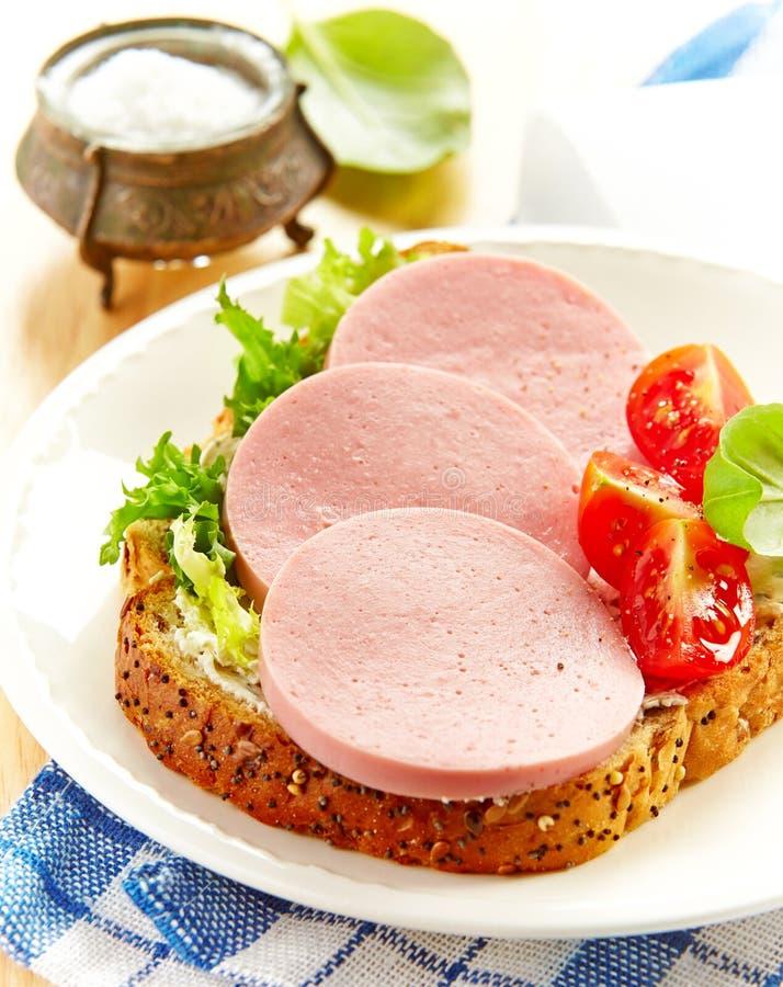 Panino con la salsiccia affettata immagini stock