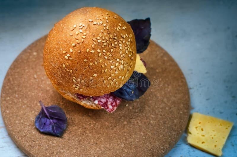 Panino con la salsiccia, il formaggio ed il basilico affumicati immagini stock