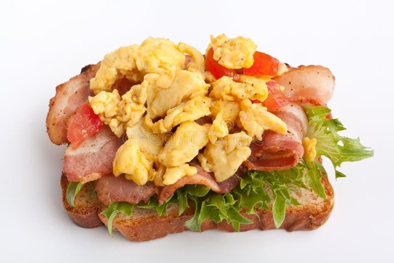 Panino con pancetta affumicata, le uova rimescolate e la lattuga immagini stock libere da diritti