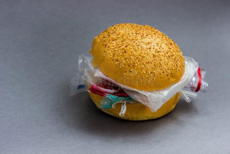 Panino con polietilene e plastica invece delle verdure e della carne Il problema di inquinamento del pianeta con plastica ecologi immagine stock libera da diritti