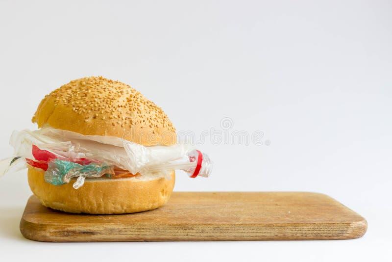 Panino con polietilene e plastica invece delle verdure e della carne Il problema di inquinamento del pianeta con plastica ecologi fotografia stock