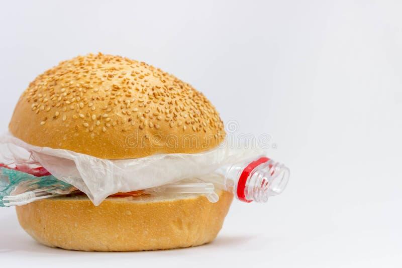 Panino con polietilene e plastica invece delle verdure e della carne Il problema di inquinamento del pianeta con plastica ecologi fotografia stock libera da diritti