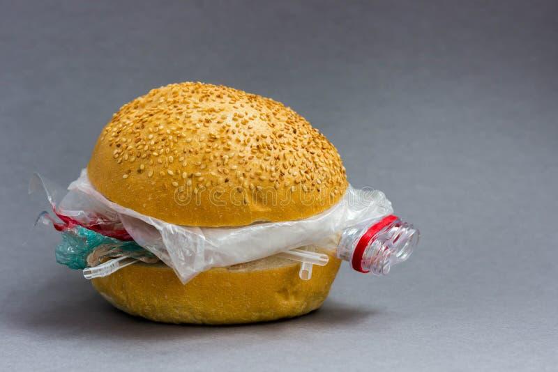 Panino con polietilene e plastica invece delle verdure e della carne Il problema di inquinamento del pianeta con plastica ecologi fotografie stock