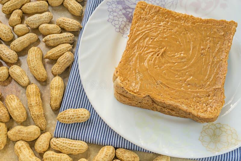Panino del burro di arachidi sul piatto bianco fotografia stock libera da diritti