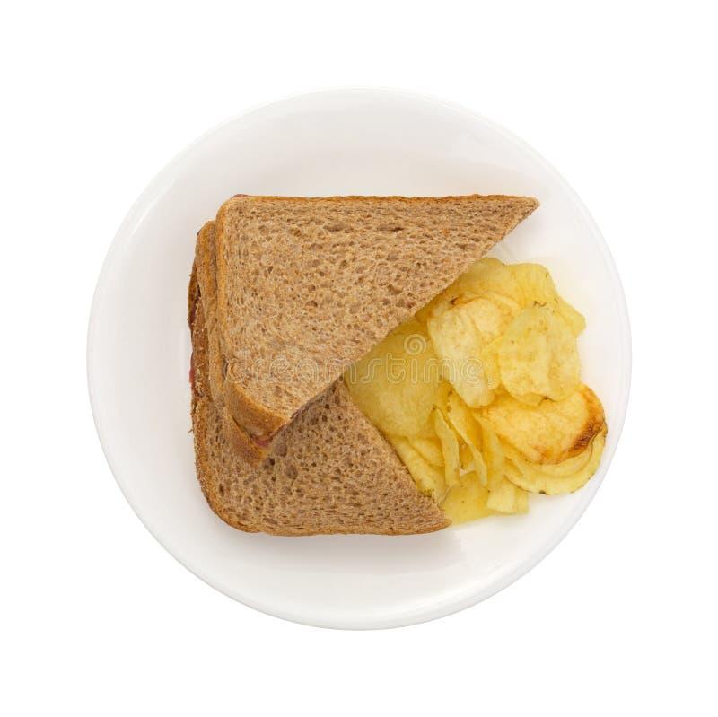 Panino del grano intero con i chip sul piatto immagine stock