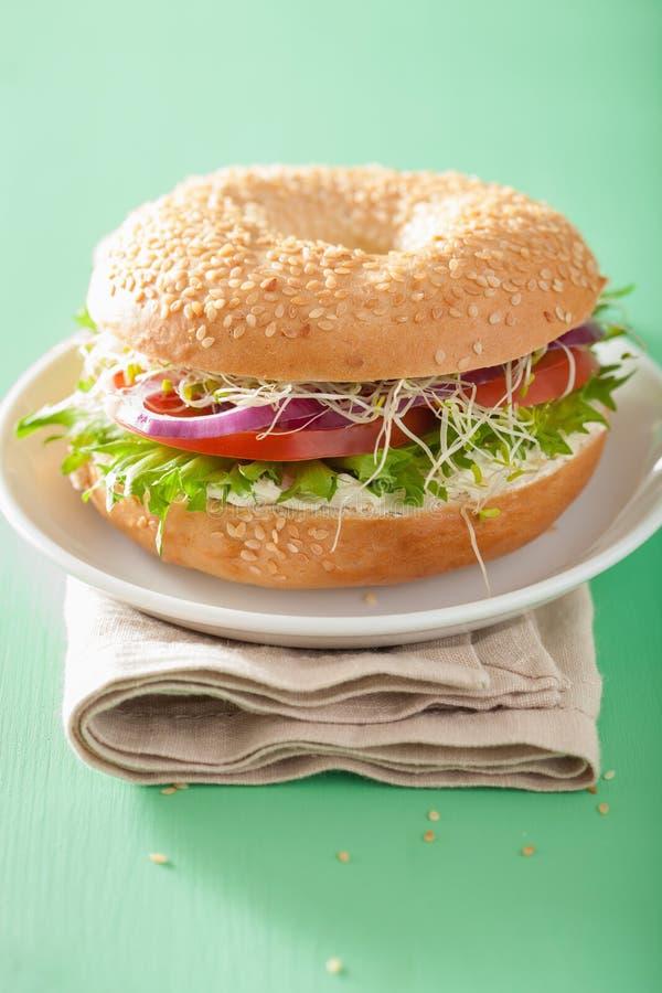Panino del pomodoro sul bagel con l'alfalfa della lattuga della cipolla del formaggio cremoso fotografia stock