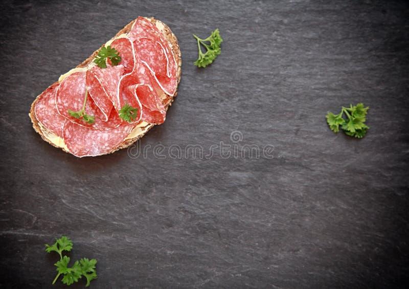 Panino del salame sull'ardesia con copyspace fotografia stock libera da diritti