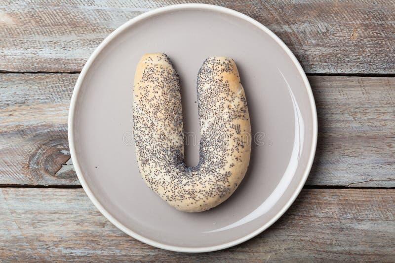 Panino dell'arco del croissant del seme di papavero sul piatto fotografia stock