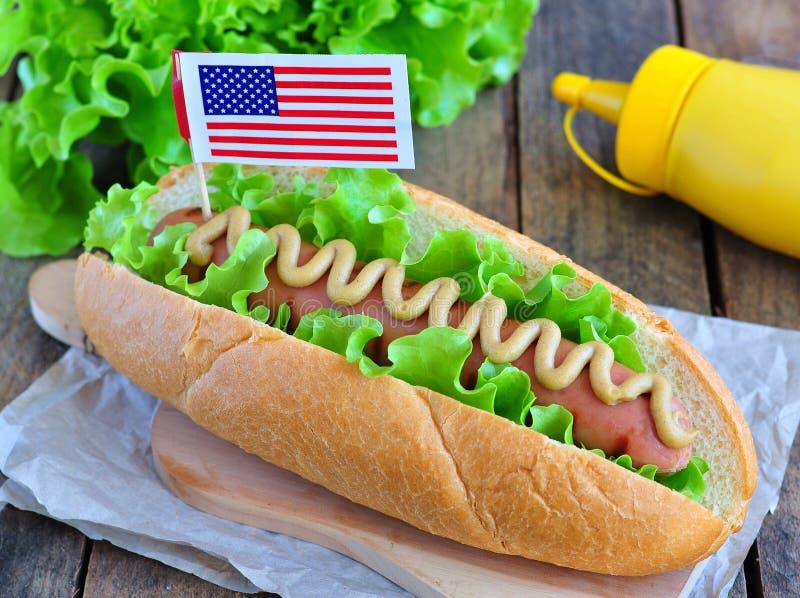 Panino dell'hot dog con la salsa e la lattuga di senape gialle fotografia stock