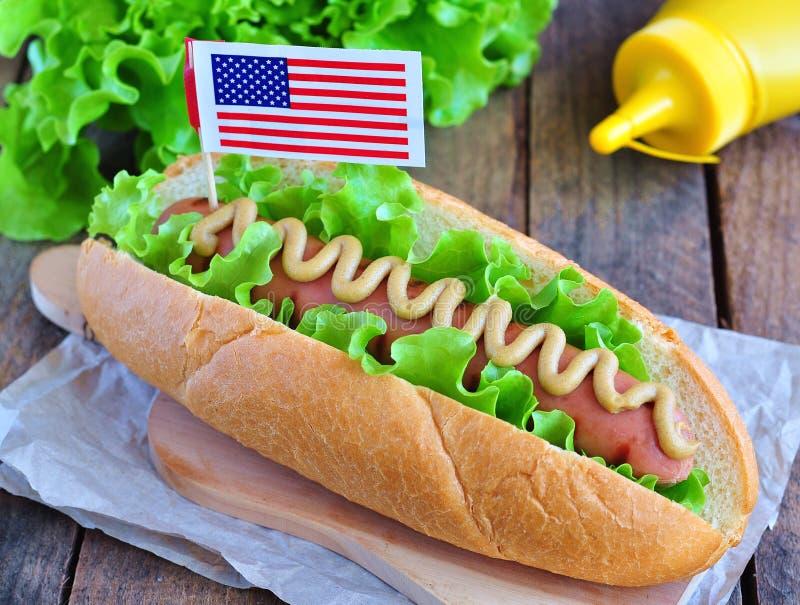Panino dell'hot dog con la salsa e la lattuga di senape gialle immagine stock