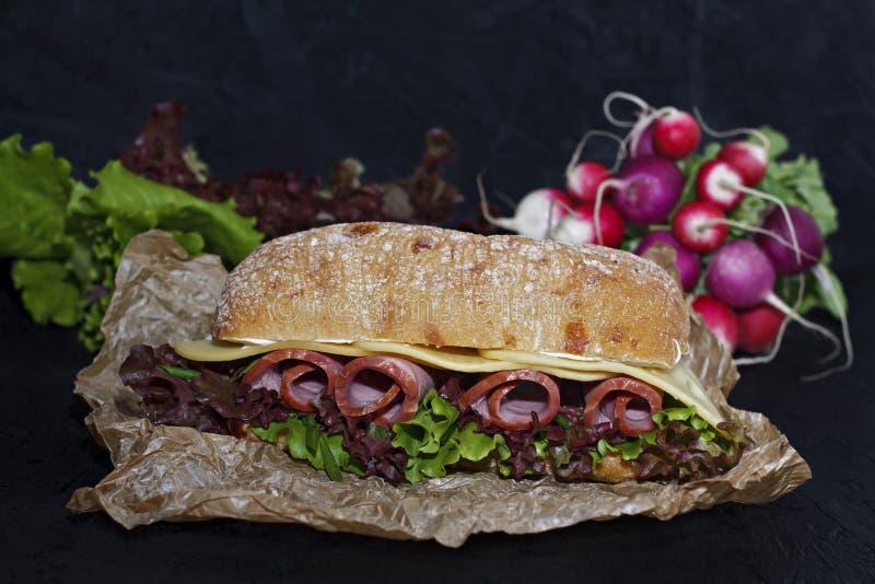 Panino della ciabatta croccante con il prosciutto, foglie della lattuga e del formaggio immagini stock libere da diritti