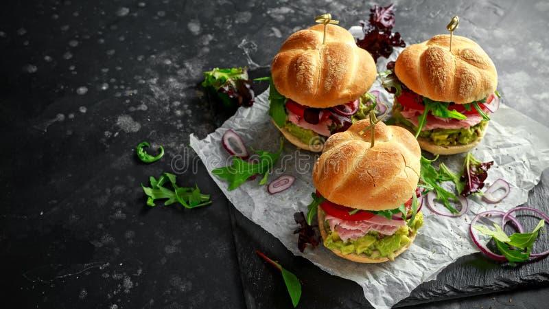 Panino domestico fresco con il guacamole dell'avocado, i pomodori, la rucola, la cipolla rossa ed il prosciutto immagine stock libera da diritti