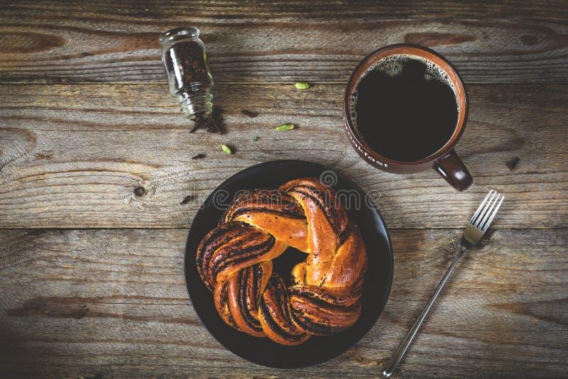 Panino e tazza dolci di caffè nero sulla tavola di legno d'annata fotografie stock libere da diritti