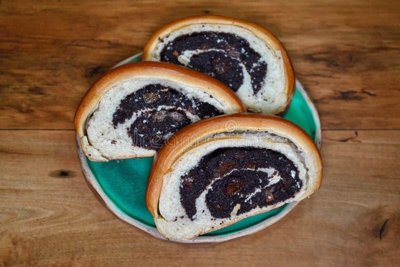 Panino fresco rubicondo affettato con i semi di papavero che si trovano su un piatto blu rotondo su una vista superiore di superf fotografia stock
