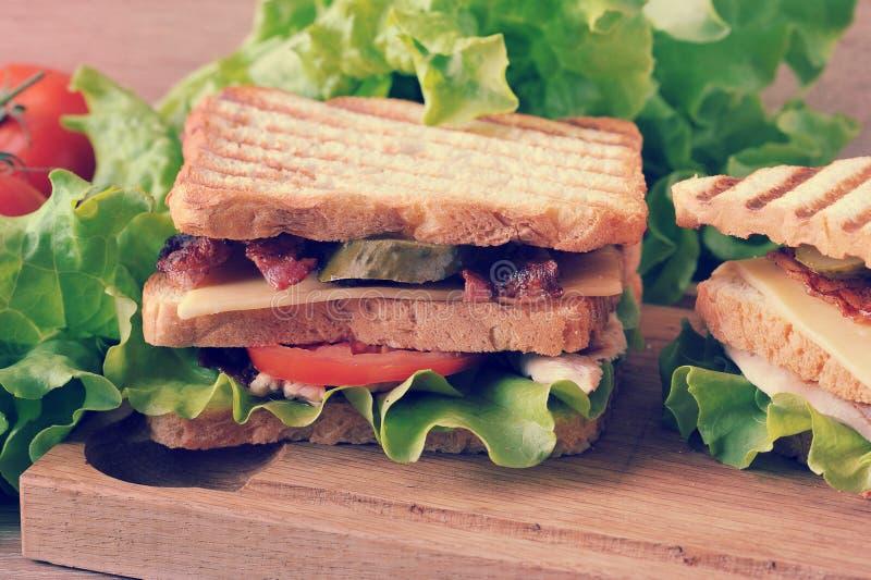 Panino a più strati con formaggio, bacon, pollo, pomodori, pic fotografie stock libere da diritti