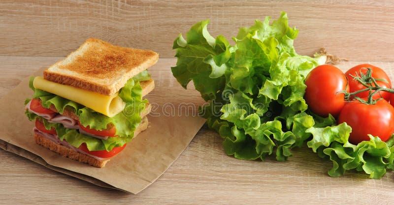 Panino a più strati con formaggio, il prosciutto, i pomodori e la lattuga fotografia stock libera da diritti