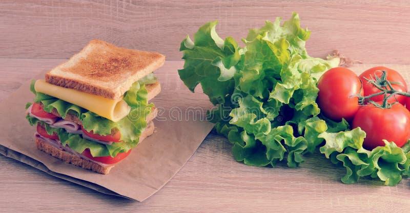 Panino a più strati con formaggio, il prosciutto, i pomodori e la lattuga fotografie stock libere da diritti