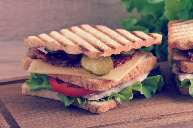 Panino a più strati con formaggio, il prosciutto, i pomodori, i sottaceti ed il le fotografie stock libere da diritti