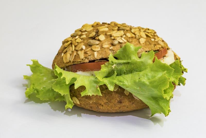 Panino pronto da mangiare con formaggio, tomatoe e lattuga verde su fondo bianco fotografie stock libere da diritti