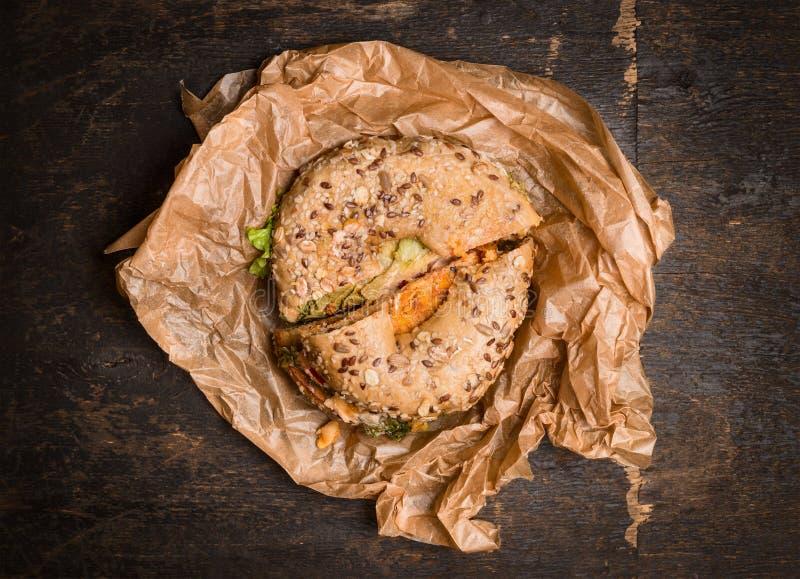 Panino su un bagel su carta da imballaggio sgualcita su fondo di legno rustico, vista superiore fotografia stock libera da diritti