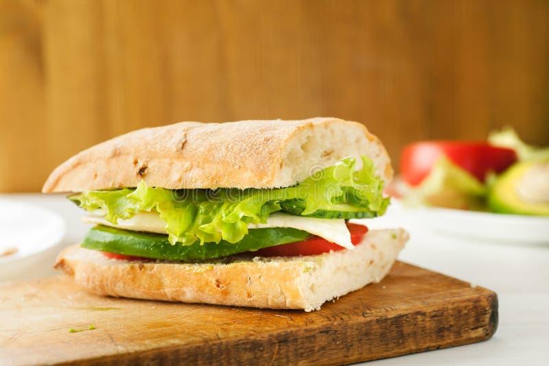 Panino vegetariano con l'avocado, il pomodoro, l'uovo e l'insalata verde su un bordo di legno immagini stock libere da diritti