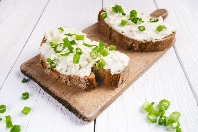 Panna av stekte ägg med tomater, ost, vårlök, örter på en vit tabell Bröd med spread Trävit bordlägger Begrepp av f royaltyfri bild